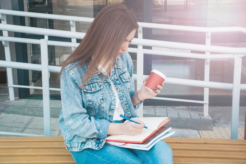 A girl in jeans clothes sits on a bench, holds notebooks, coffee and writes. The girl smiles, studies in the open air and drinks. Coffee stock images