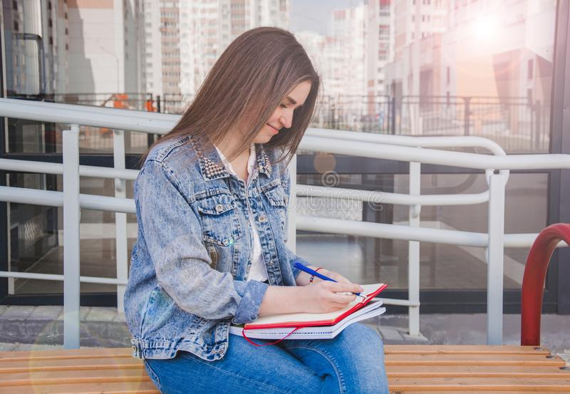 A girl in jeans clothes sits on a bench, holds notebooks and writes. On the street, she writes in a notebook, studying in the. Fresh air. Summer and denim royalty free stock image