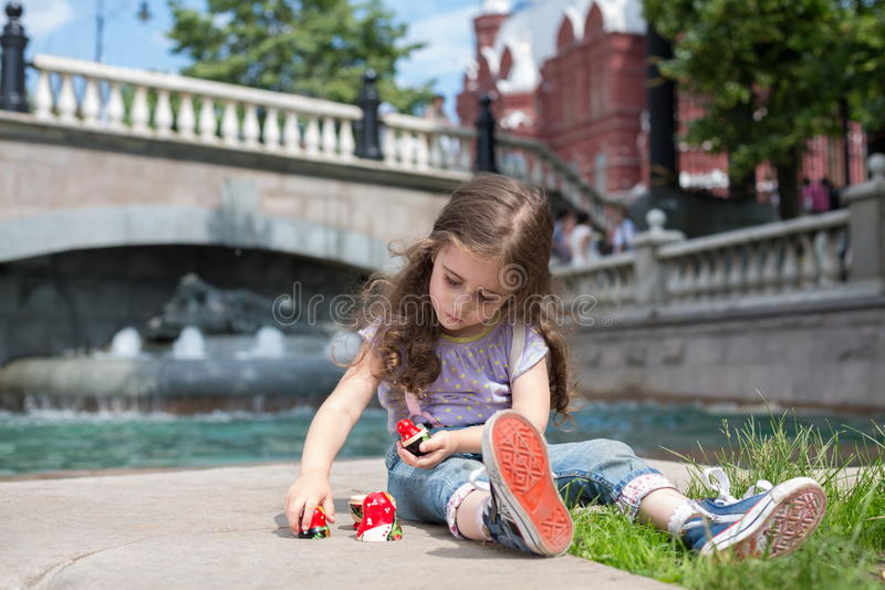 Girl in jeans sits near the fountain and play. With russian matrioshka royalty free stock images
