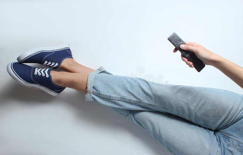The girl in jeans and sneakers sits on a white background royalty free stock image