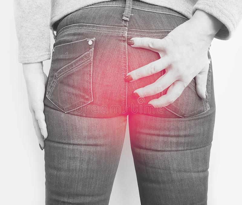 Girl in jeans suffers from hemorrhoids. Problem stock images