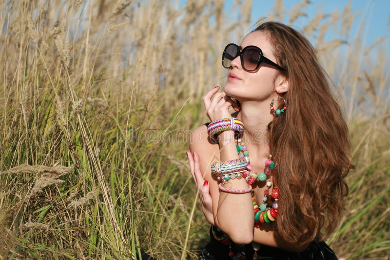 Download Girl With Jewelry And Glasses Sits In Grass Field Stock Photo - Image of female, blue: 23259206