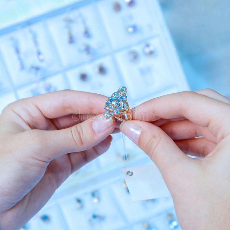 A girl in a jewelry store is holding a gold ring with diamonds. Square frame Toning in blue stock photo