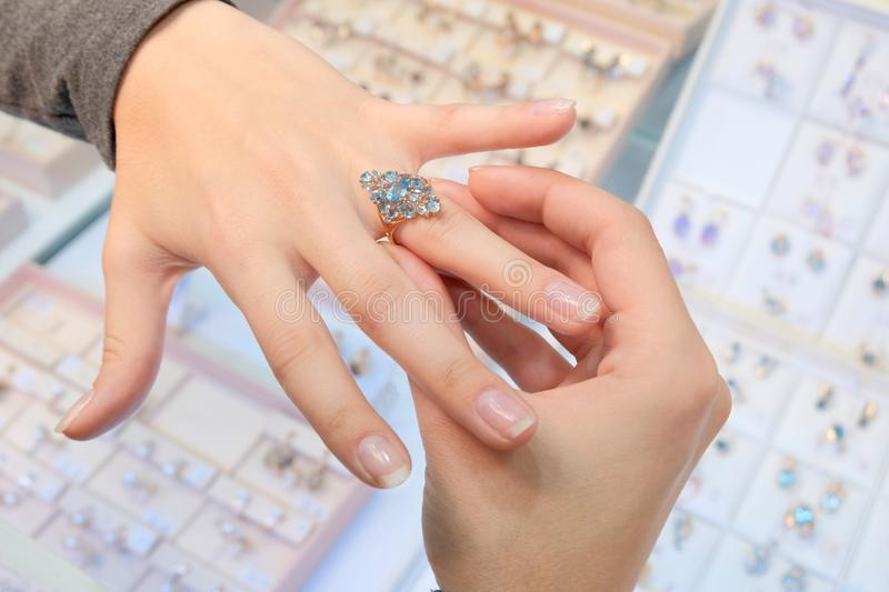 A girl in a jewelry store tries on her finger a gold ring with diamonds on the background of a shop window. Buying and shopping. stock photos