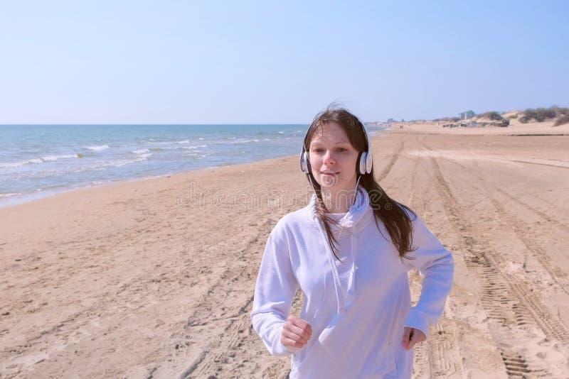 Girl jogging in headphones listen music stop run to catch breath sport outdoor. Portrait of brunette girl is jogging on sea sand beach in headphones listening stock photos