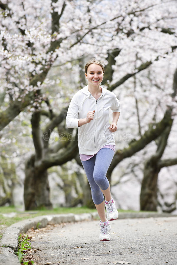 Girl jogging in park royalty free stock images