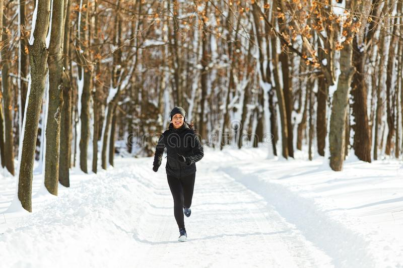 Girl jogging in the snow on the nature in winter royalty free stock photo