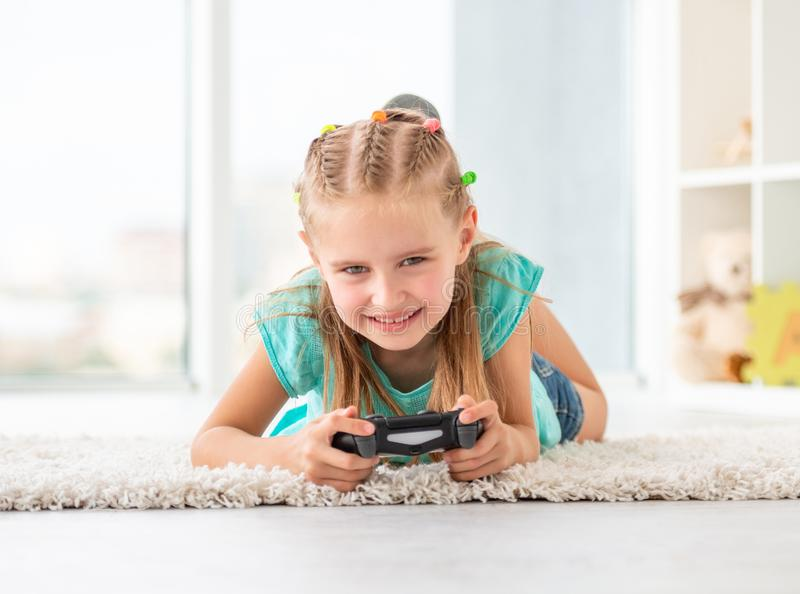 Girl with joystick. Smiling girl with joystick lying on floor in playing room royalty free stock photography