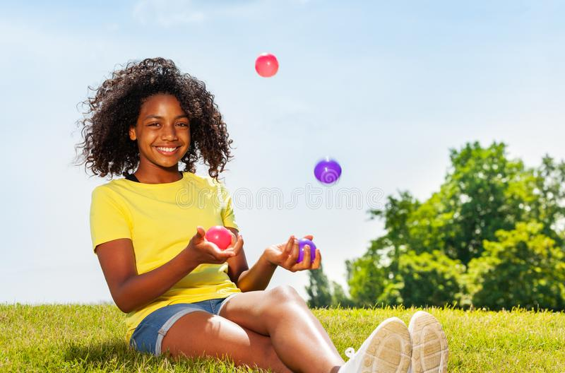 Girl juggle with balls on the lawn in park smiling royalty free stock photo