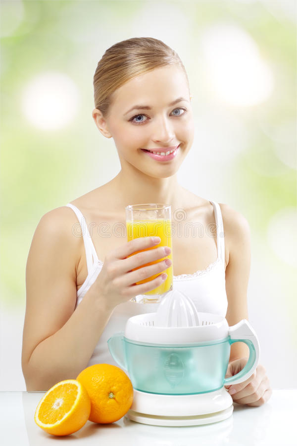 Girl With A Juicer And Orange Juice Stock Photography