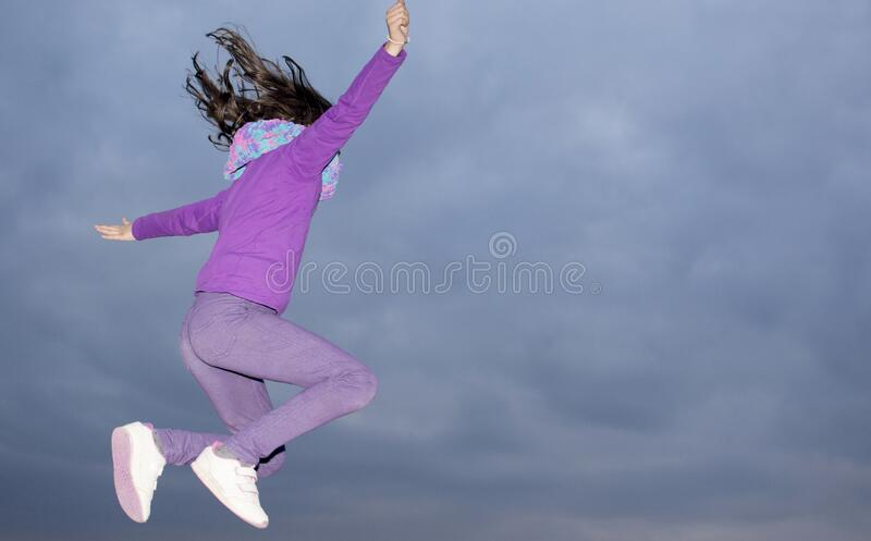 Girl jumping in the air on a winter`s night royalty free stock image