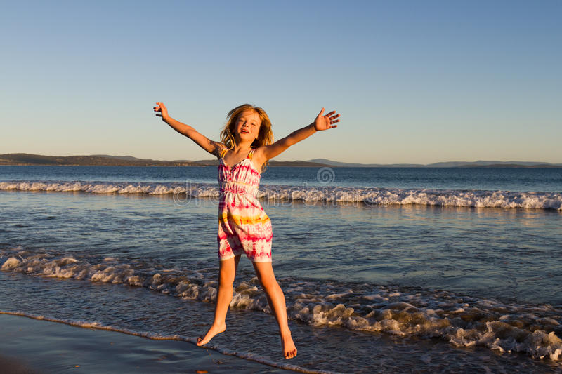 Girl jumping on beach. Lovely little girl in a dress jumping for joy in the waves at the beach royalty free stock image