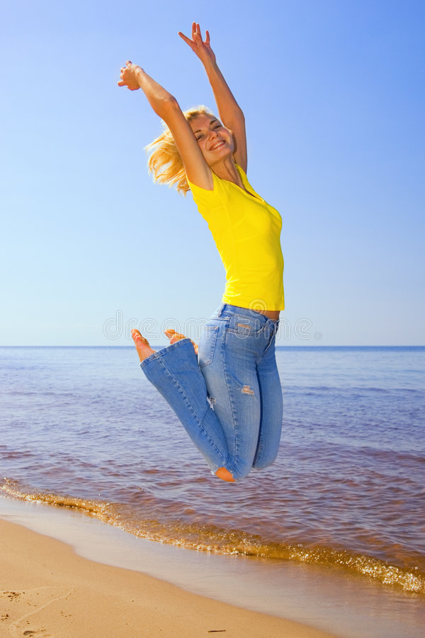 Girl jumping on the beach royalty free stock photo