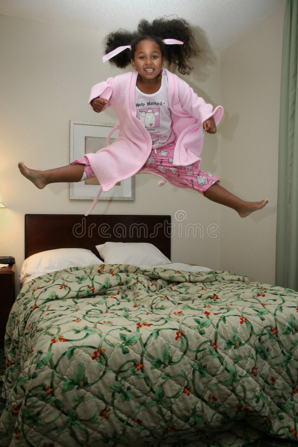 Girl jumping on bed. Cute young girl jumping on bed stock image