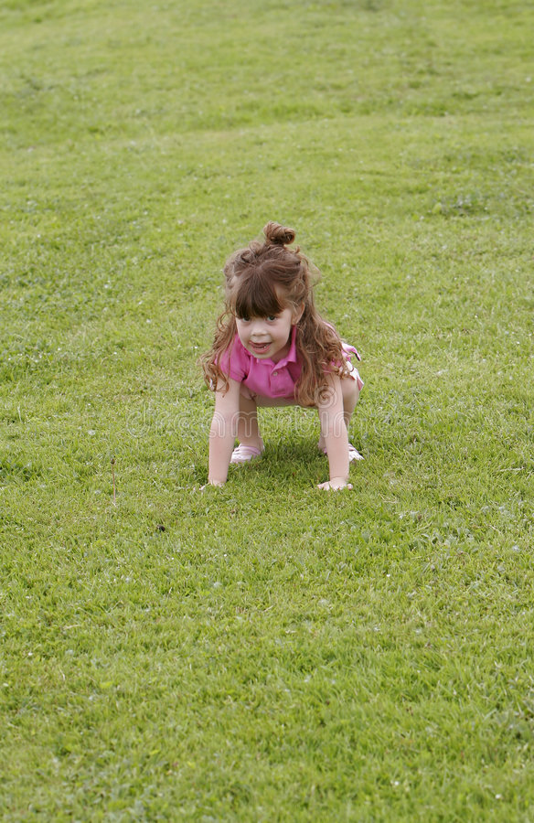 Girl jumping in grass stock photo