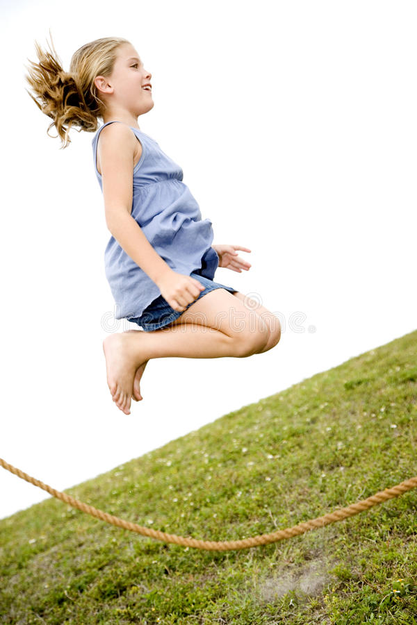 girl jumping high in air over skipping rope stock photos