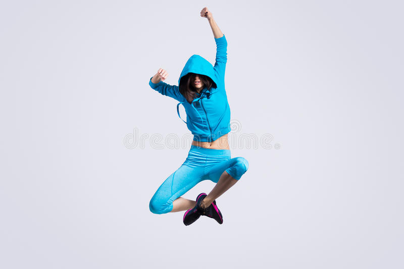 Girl jumping in hoodie sweatshirt. One beautiful young fit modern dancer lady in blue sportswear hoodie sweater working out, dancing and jumping, full length royalty free stock images