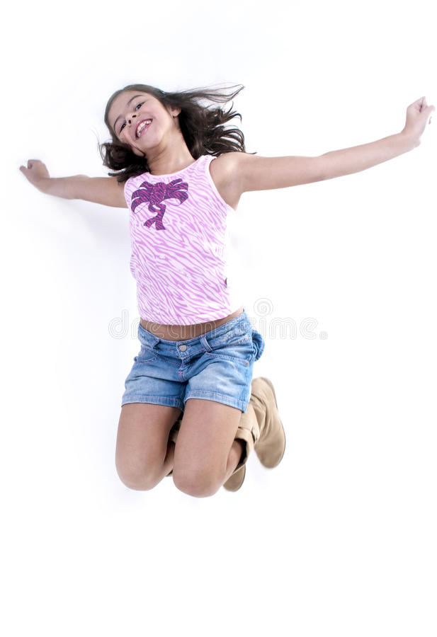 Girl jumping for joy. Cute young hispanic girl jumping for joy with outstretched arms; isolated on white background stock photos