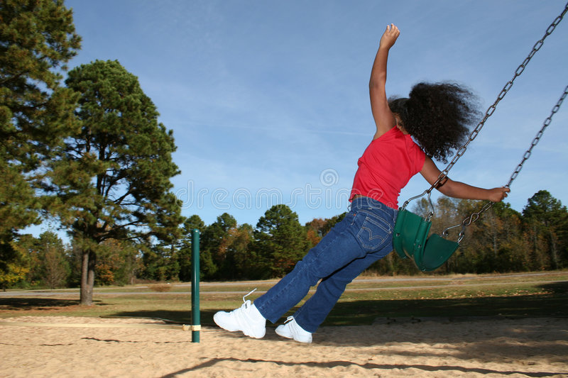 Girl jumping off swing. Rear view of multiracial girl jumping off park swing stock photography
