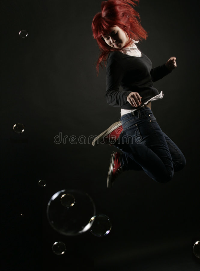 Girl jumping over bubbles royalty free stock images