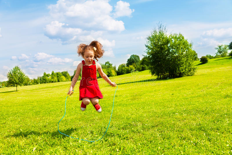 Girl jumping over the rope. Beautiful little 6 years old girl jumping over the rope in the park on sunny summer day royalty free stock photos