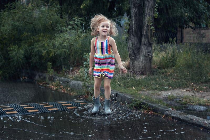 Girl jumping in the rain stock photos
