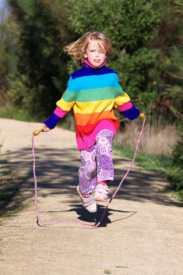 Girl jumping rope. A cute little girl jumping with her skipping rope royalty free stock photos