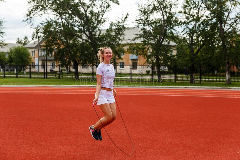 Girl jumping rope at the stadium stock image