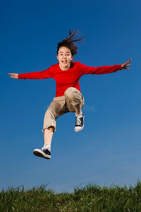 Girl jumping, running against blue sky stock photography