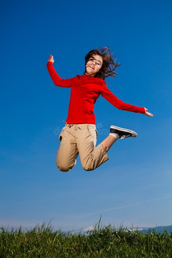 Girl jumping, running against blue sky stock photos