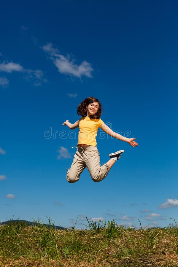 Girl jumping, running against blue sky. Happy girl jumping, running against blue sky stock photos