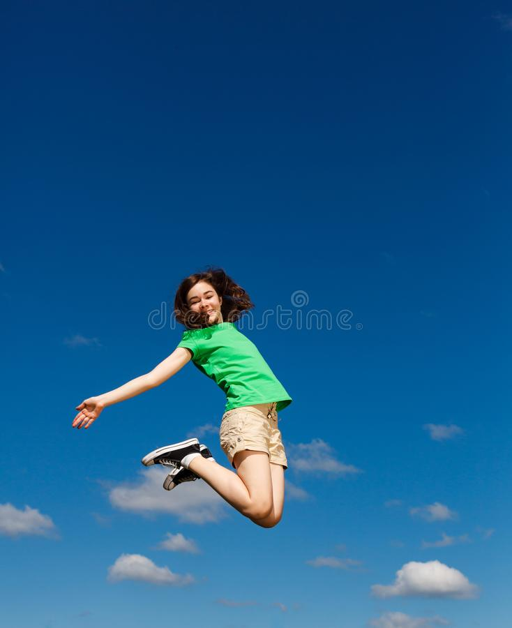 Girl jumping, running against blue sky. Happy girl jumping, running against blue sky royalty free stock photo