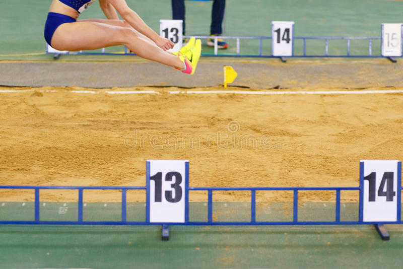 Girl jumping into sandpit on long jump competition. Sportswoman jumping into sandpit on triple jump competition in track and field championship stock images