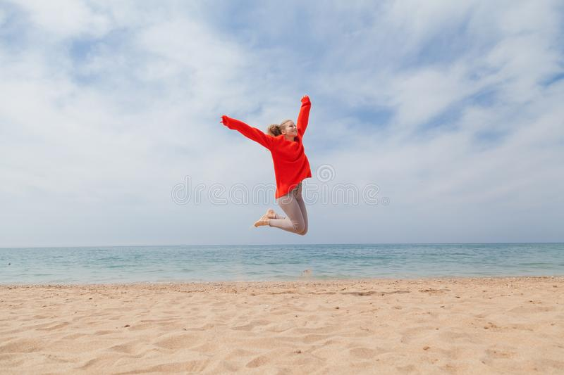 Girl jumping on a sandy beach sea shore. 1 stock photo