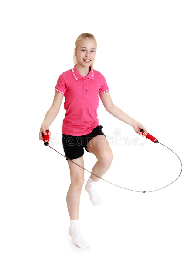 Girl jumping skipping rope. Beautiful blond girl with gray eyes jumping rope. The girl wearing the pink Jersey with short sleeves and short black shorts-Isolated stock photography