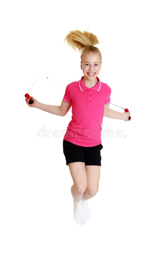Girl jumping skipping rope. Beautiful blond girl with gray eyes jumping rope. The girl wearing the pink Jersey with short sleeves and short black shorts-Isolated stock image