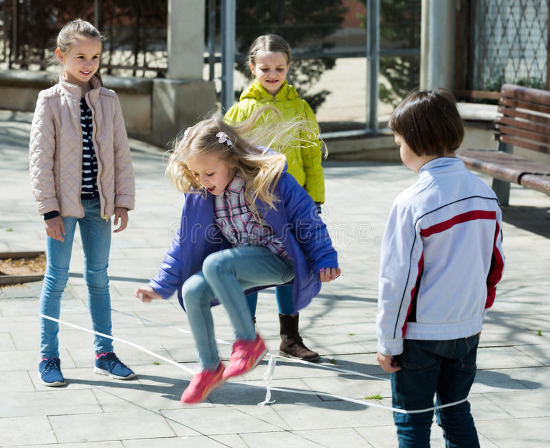 Girl jumping with skipping rope among friends. Outdoor royalty free stock photography