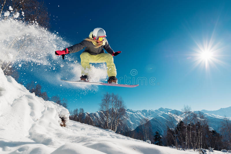 Girl is jumping with snowboard stock image