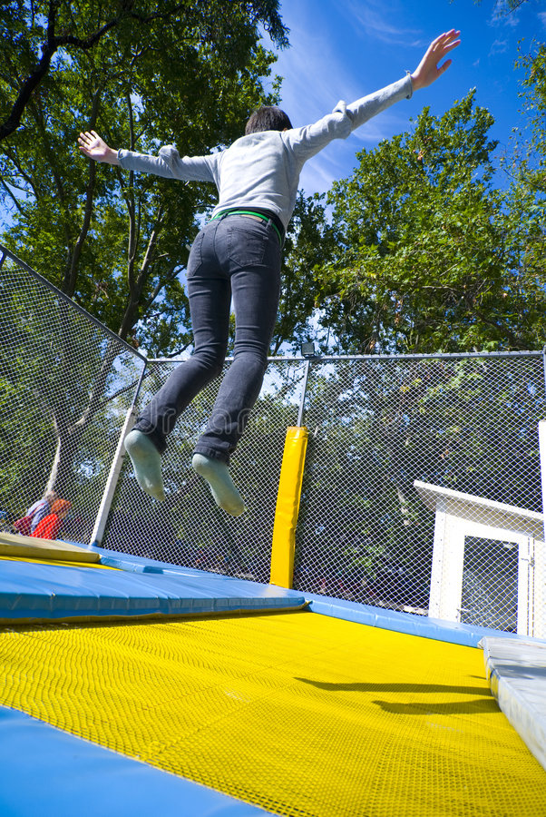 Girl jumping on trampoline. stock images