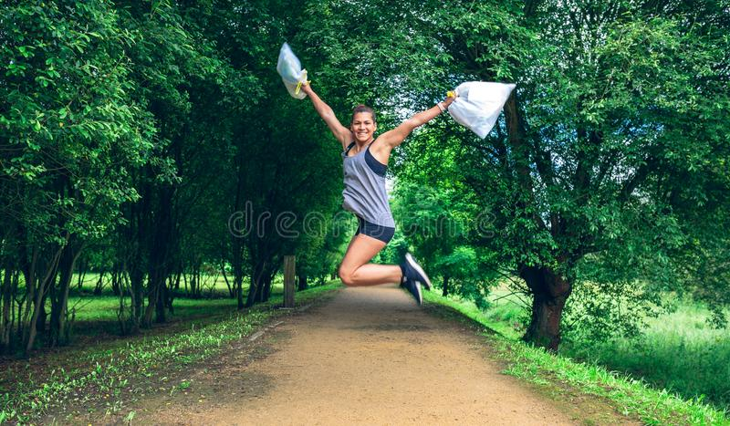 Girl jumping with trash bags after plogging royalty free stock image