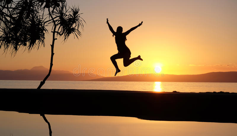 Girl jumping at the waterpool on the beach against the sunset royalty free stock photo