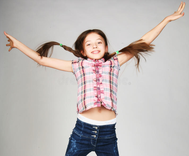 girl jumps on a gray background stock image