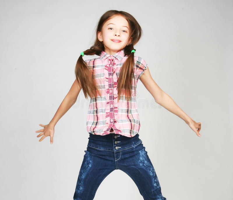 Girl jumps on a gray background royalty free stock image