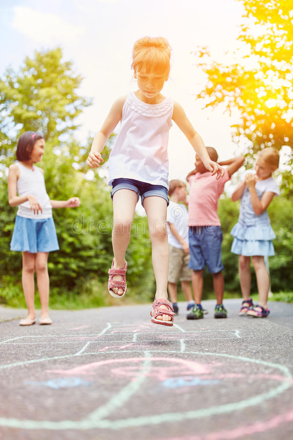 Girl jumps during hopscotch game royalty free stock photos