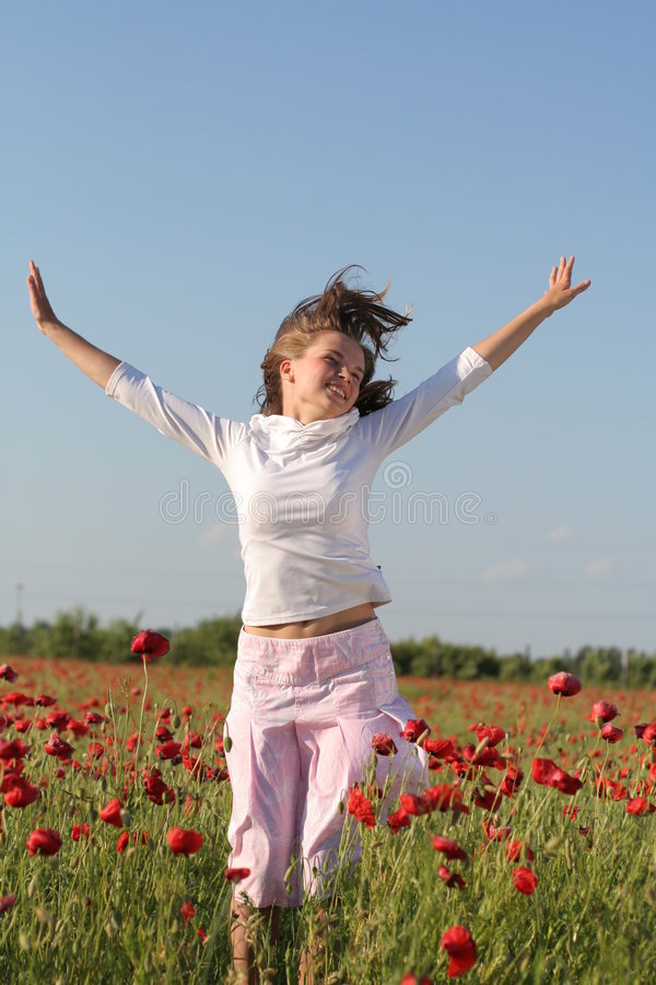 Girl jumps over poppy field royalty free stock photo