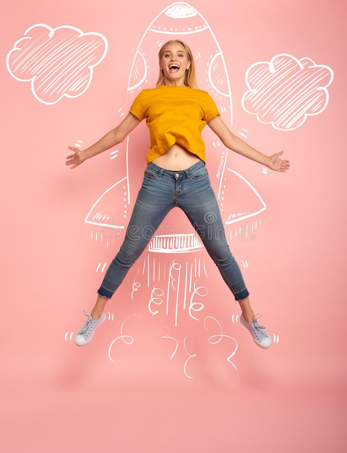 Girl jumps on pink background ready to fly like a rocket. Concept of freedom, energy and vitality stock images
