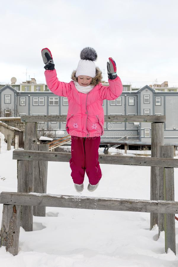 Girl jumps from wooden bench royalty free stock photography