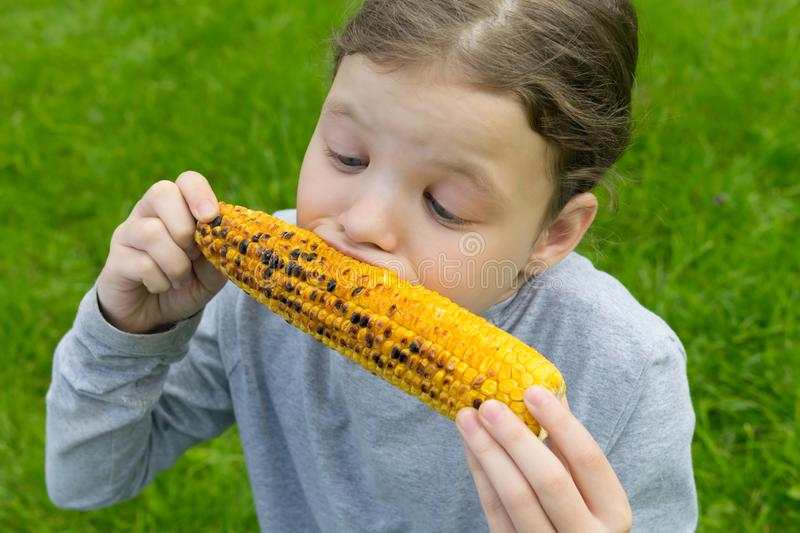 The girl keeps  hands an ear of corn and bites with appetite, against the green lawn stock photography