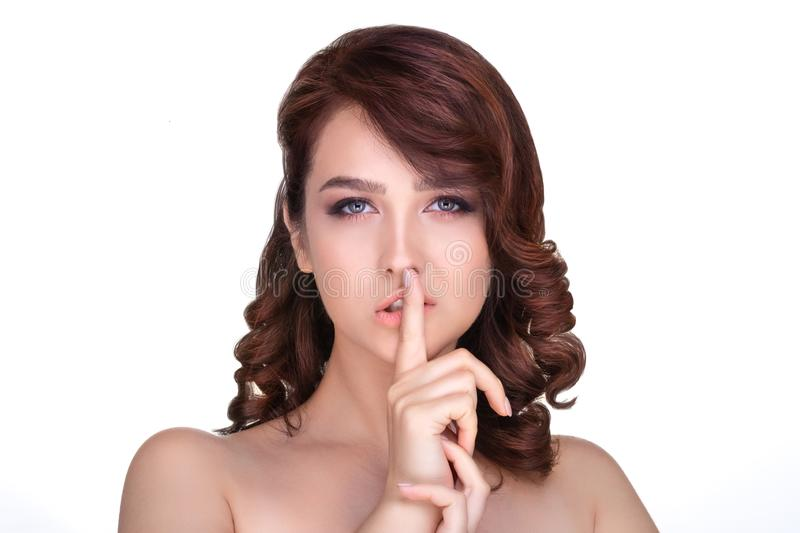 The girl keeps her finger on her lips. Sign quiet stock photography