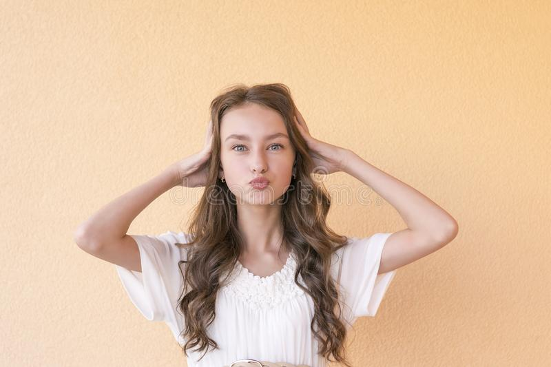 Girl keeps lips as going to kiss someone. Beautiful young girl keeps lips as going to kiss someone. Expresses his love to someone. Happy woman against orange royalty free stock image